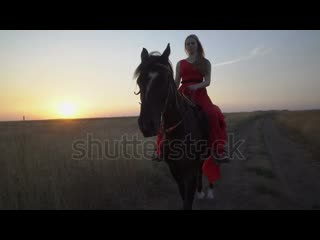 Stock-footage-young-girl-horseback-rider-in-red-dress-riding-horse-on-country-road-in-evening